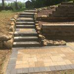 hardscape masonry walkway leading to a stone patio and retaining wall